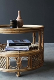 Lifestyle image of the Round Bamboo Coffee Table on a dark background