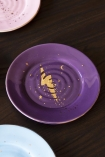 Close-up detail image of the purple plate with a gold illustration of a lightning bolt on black surface with other plates in background