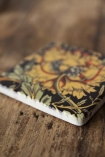 Close-up detail image of one of the Vintage Style Floral Ceramic Coasters on wooden surface