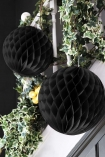 lifestyle image of Set Of 2 Honeycomb Ball Decorations - Black hanging from white Bannister with ivy