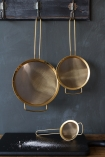 lifestyle image of Set Of 3 Gold Metal Sieves hanging from black shelf over black board with flour on and grey wall background