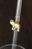 Close up detail image of gold elephant charm hanging from transparent drinking straw with dark wall background