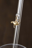 Close up detail image of gold ostrich charm hanging from transparent drinking straw on dark wall background