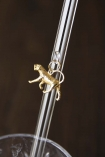 Close up detail image of gold monkey charm hanging from transparent drinking straw on dark wall background