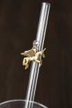 Close up of gold unicorn charm hanging from transparent drinking straw