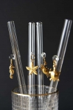 Collection of 4 drinking straws in a glass showing all 4 golden sea-life charms