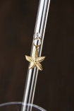 Close up detail image of gold starfish charm hanging from transparent drinking straw with dark wall background