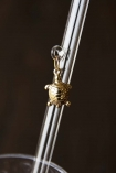 Close up detail image of gold turtle charm hanging from transparent drinking straw dark wall background