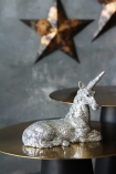lifestyle image of Silver Sparkle Unicorn Ornament on gold side table with copper effect stars on grey wall background