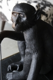 detail image of face on Sitting Monkey Table Lamp - Black - Suitable For Outdoors with black and white cowhide armchair in background