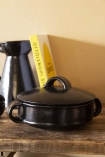 Lifestyle image of the Black Brown Terracotta Casserole Dish - Small with the lid on