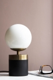 Lifestyle image of the Atlas Globe Table Lamp With Black & Brass Base switched off on white table and pale wall background