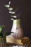 Busy lifestyle image of the Botanical Bottle Neck Vase with books on table and plants in vases with dark wall background