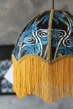 detail image of Anna Hayman Designs DecoFabulous Blue Dianne Pendant Shade with black and blue art print in background on distressed grey wall background