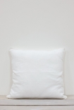 lifestyle image of Lisbon Soft Linen Cushion - White on floor with white wall background