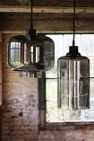 lifestyle image of Smoked Glass Pendant Ceiling Light - Cylinder and second light with rustic brick wall background