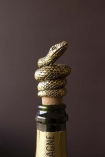 Lifestyle image of the Antique Gold Snake Bottle Stopper in a bottle