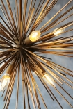 detail image of Starburst Brass Beam Pendant Lamp with grey wall background