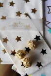 lifestyle image of Set Of 24 Foil Stars Treat Bags with gold chocolates on top on gold table