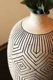 Close-up detail image of the neck of the Stone & Black African Ceramic Bottle Vase on black side table with eucalyptus inside and cloisters painted wall background