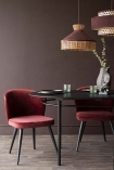 Lifestyle image of the Sungkai Wood Black Oval Dining Table with Deco Velvet Dining Chairs in Merlot Red and rattan ceiling lights with briarwood painted wall background and dark wooden flooring