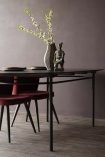 Lifestyle image of the Sungkai Wood Black Oval Dining Table with red dining chairs and vase with briarwood painted wall background and dark wooden flooring