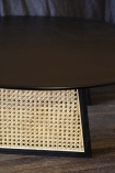 Close-up detail image of the Sungkai Woven Cane Round Coffee Table on dark wooden flooring