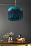 Panned out lifestyle image of the Bespoke Teal Silk Tiffany Lamp Shade with wavy fringe over chest of drawers with ornaments on with dark wall background