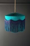 lifestyle Image of the Bespoke Teal Silk Tiffany Lamp Shade with wavy fringe on dark wall background