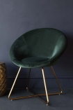 On it's own lifestyle image of the The Grand Velvet Circular Dining Chair in Rich Green on dark flooring and dark blue wall background