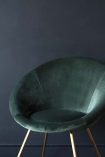 Close-up detail image of the seat on The Grand Velvet Circular Dining Chair in Rich Green with dark blue wall background