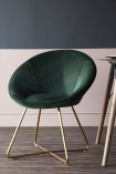 Dining lifestyle image of the The Grand Velvet Circular Dining Chair in Rich Green with table in background on wooden floor and contrasting wall background