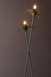 Close-up image of the lights on the Two Palm Reeds Floor Lamp lit up on dark wall background
