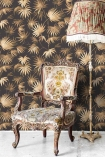 Lifestyle image of the Va Va Frome Noir Black Wallpaper by Pearl Lowe with patterned chair and floor lamp