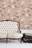Lifestyle image of the Va Va Frome Powder Pink Wallpaper by Pearl Lowe with white sofa and brown suitcases