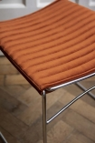 Close-up image of the ribbed velvet on the seat of the Chrome & Velvet Stackable Dining Chair In Rich Rust