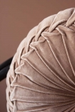 Close-up detail image of the Vintage Style Velvet Rouched Round Cushion in Soft Pink on black rattan chair with emanuella painted wall background