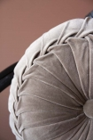 Close-up detail image of the Vintage Style Velvet Rouched Round Cushion in Taupe on black rattan chair with emanuella painted wall background