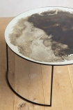 Close-up detail image of the Vintaged Glass Mirror & Iron Round Coffee Table on pale wooden floor and white wall background