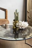 Close-up detail lifestyle image of the Vintaged Glass Mirror & Iron Round Coffee Table with coral and vases on tbale and armchair in background with pale wooden floor and pale wall