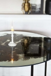 Close-up image of the Vintaged Glass Mirror & Iron Round Dining Table with white candlestick in centre