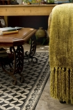 lifestyle image of Beija Vinyl Floor Runner - Sofi Antique with wooden coffee table and sofa with mustard blanket on top