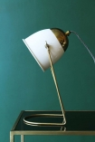 detail image of White & Brass Lola Desk Lamp on black and gold table with teal wall background