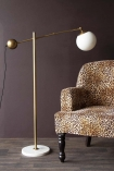 Lifestyle image of the Atlas Globe Angled Floor Lamp With Marble Base switched off with Rockett St George Leopard Love Armchair on dark wooden flooring and dark purple wall background