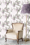 Lifestyle image of the Wisteria Lilac Wallpaper by Pearl Lowe with nude and wooden armchair and purple floor lamp