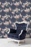 Lifestyle image of the Wisteria Midnight Mint Wallpaper by Pearl Lowe with blue and white arm chair and white flooring