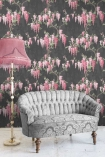 Lifestyle image of the Wisteria Noir Black Wallpaper by Pearl Lowe with grey sofa and pink floor lamp