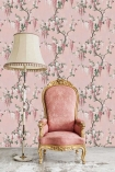 Lifestyle image of the Wisteria Pink Bloom Wallpaper by Pearl Lowe with pink and gold velvet chair and white floor lamp