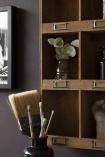Lifestyle close-up of the corner of the Traditional Pigeon Hole Wooden Storage Wall Unit filled with accessories and on a dark wall background with paintbrushes in foreground