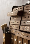 Close-up lifestyle image of the Traditional Apothecary Cabinet Style Wooden Storage Wall Unit with distressed grey wall background